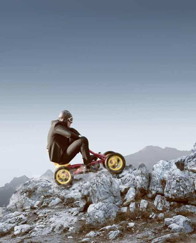 homme sur une voiture à pédale voulant gravir la montagne